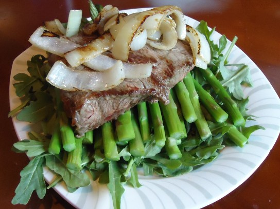 Grass Fed Steak With Caramelized Onions Over Asparagus And Arugala